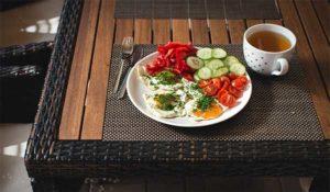 тарелка с яичницей и овощами на столе