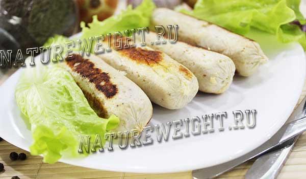 куриные сосиски домашние на тарелке с зеленью